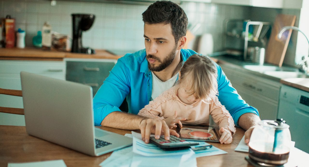 dad calculating child support while holding daughter