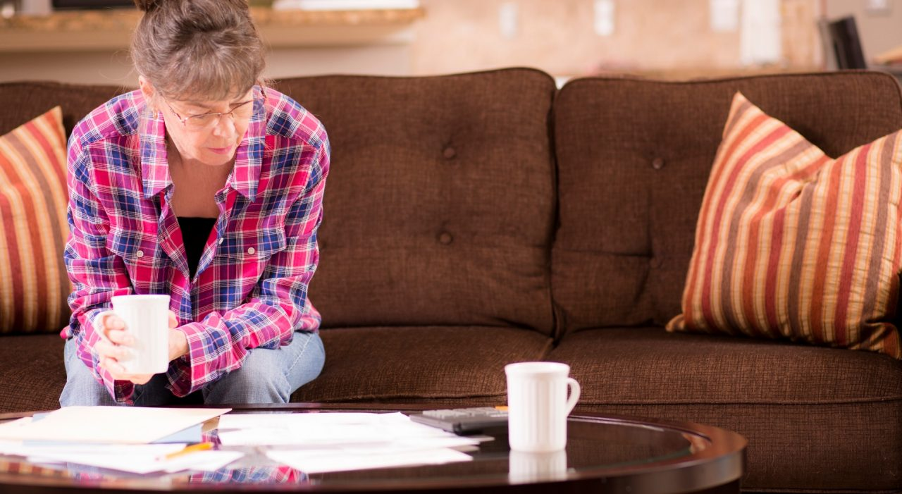 Senior adult worries over eviction notice while sitting on a living room sofa.  A pile of foreclosure paperwork and a 90-day written notice are on the coffee table.