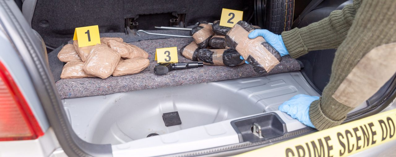 Police pull drugs out of a car at at drug trafficking crime scene