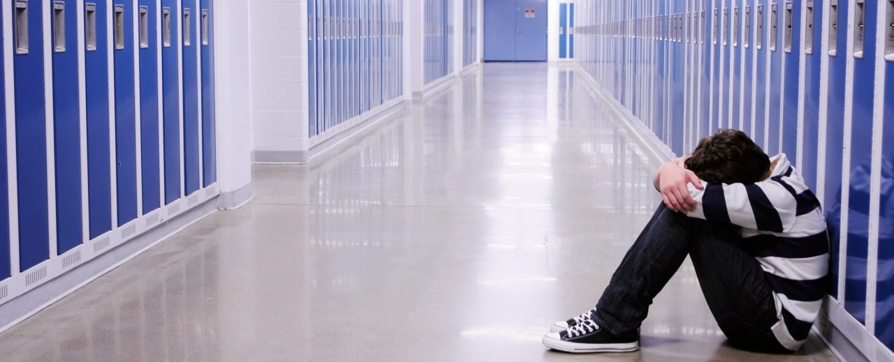 Bullied child sitting with knees up and head down in empty high school hallway