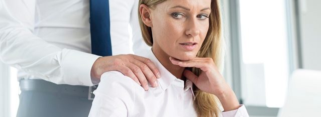Woman uncomfortable with man's hand on her shoulder while sitting at a laptop at work