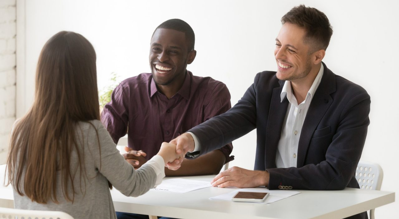 Smiling multiracial hr handshaking female applicant won job interview, friendly diverse executives and successful candidate shaking hands offering employment contract, recruiting and hiring concept