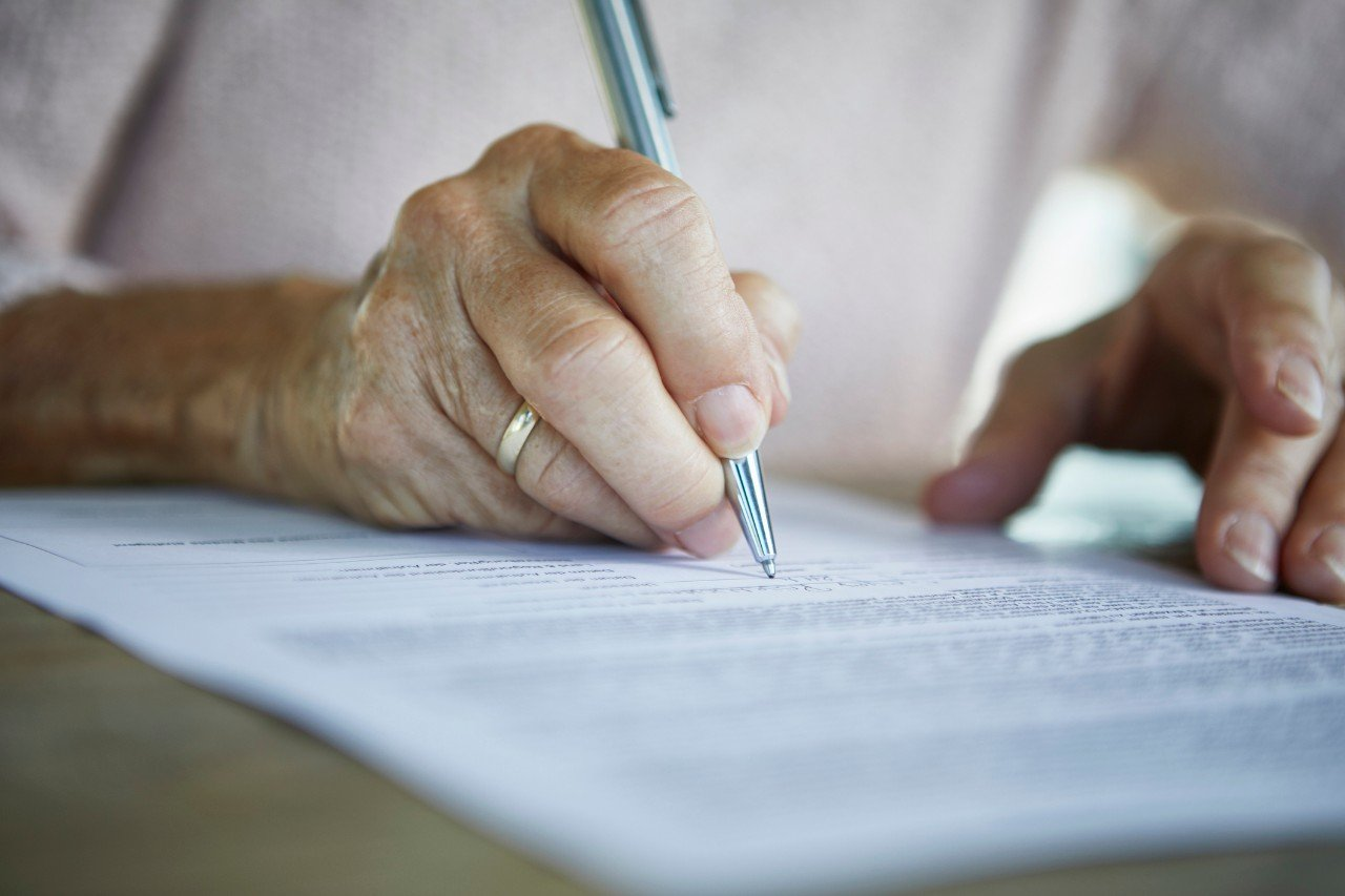 Older woman's hands are holding a pen, signing a will.