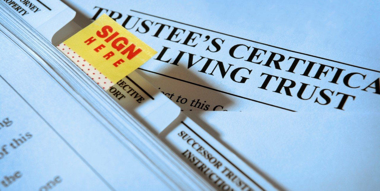 """""""Sign Here"""" tab on living trust documents."""