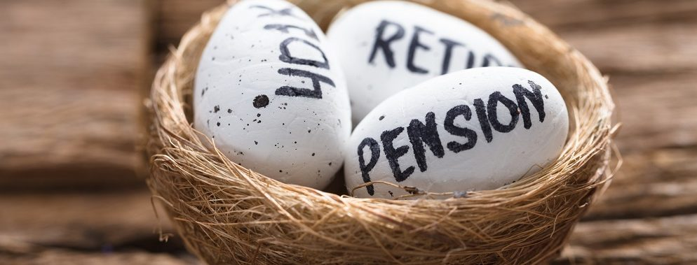 "Closeup of ""pension,"" ""401(k),"" and ""retire"" written on white eggs in nest on wood"