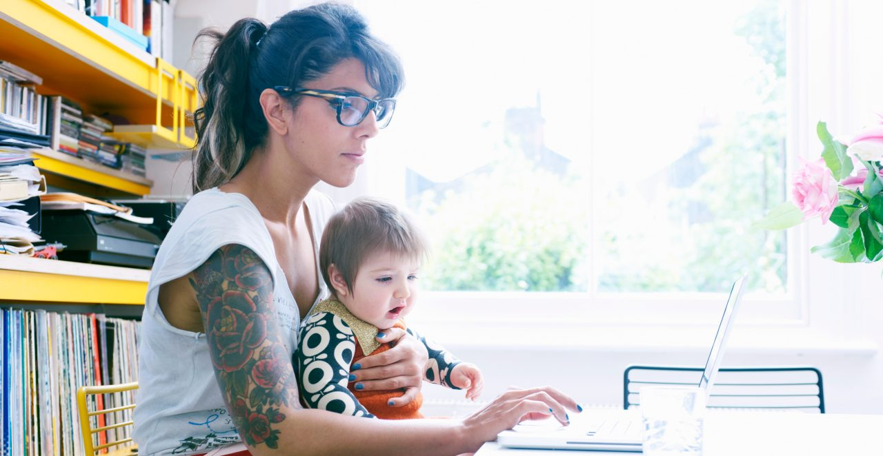Mom Holding Young Child While Researching Divorce Options