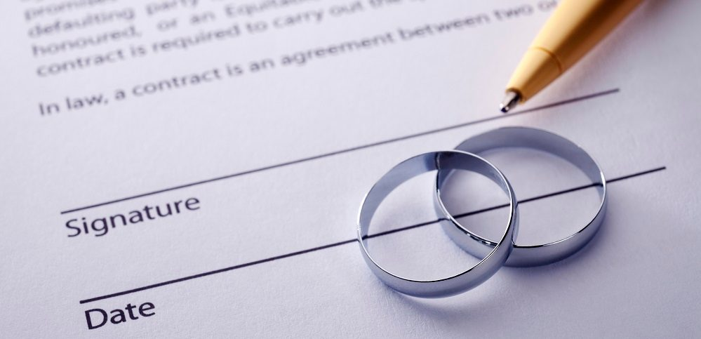 Wedding certificate with two rings and a pen for marriage name change