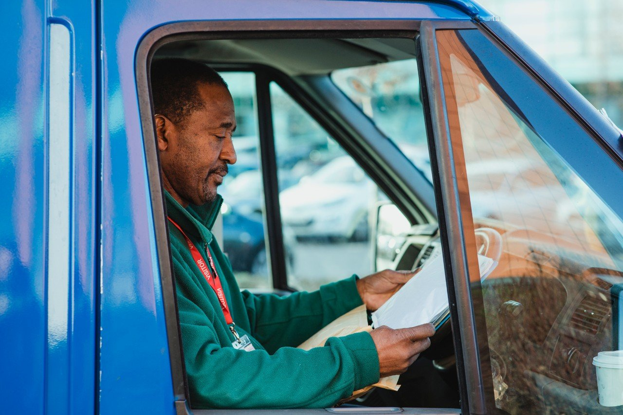 An independent contractor working on a clipboard in a vehicle