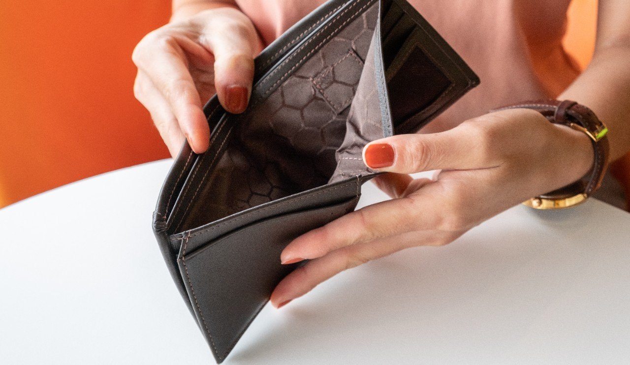 Person checking empty wallet when they owe money