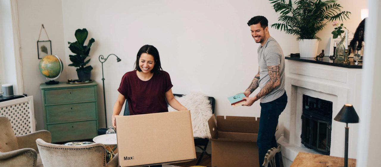 two people unpacking boxes in living room at new home