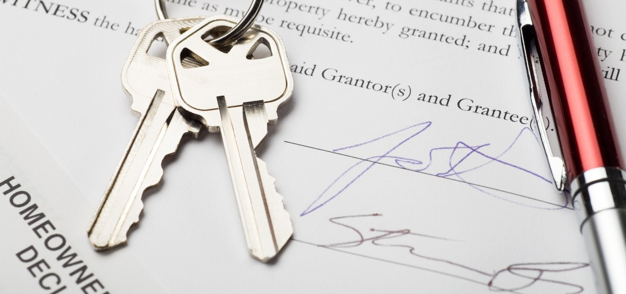 Types of home ownership: House keys with signed settlement document and pen