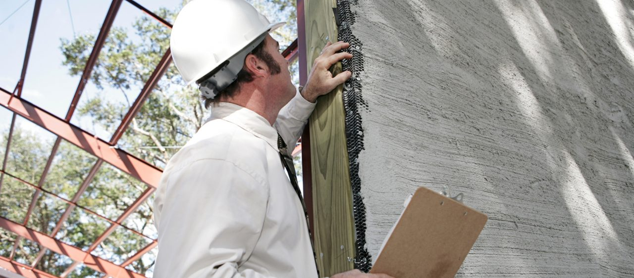 A building inspector looking at a possible construction error (incomplete stucco).
