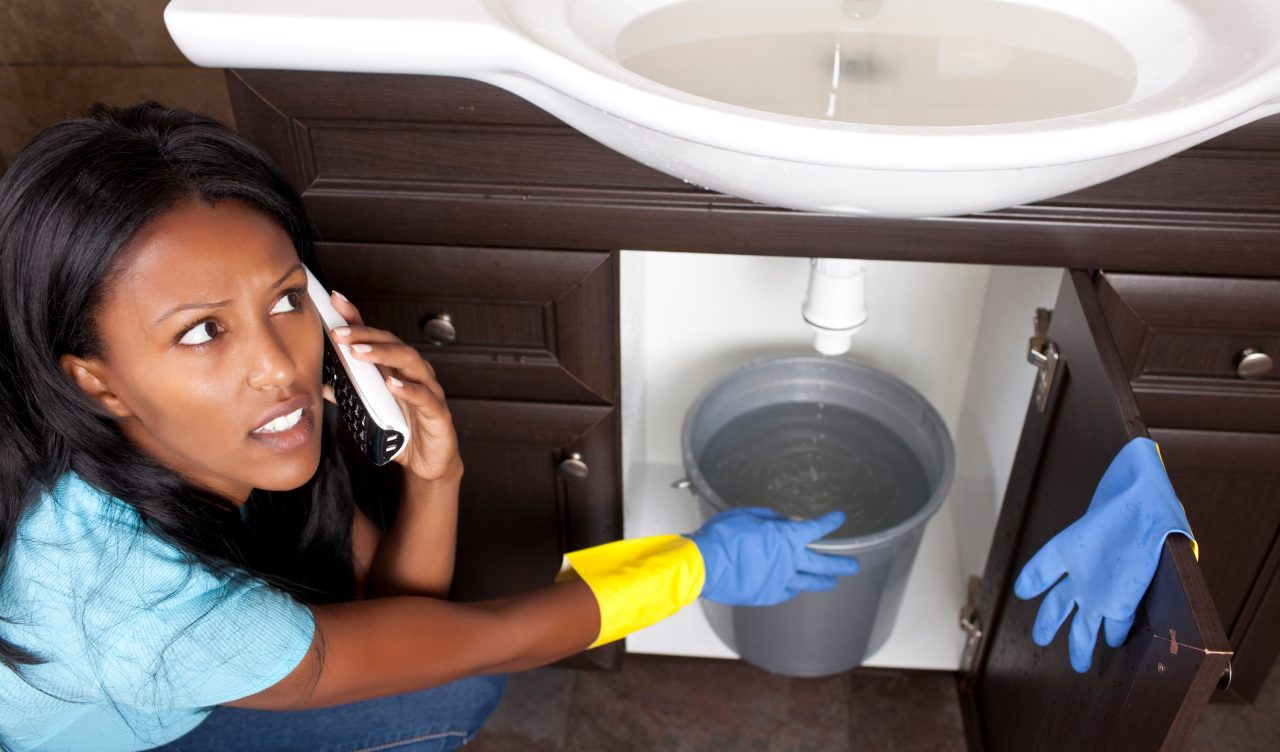 Woman calling her landlord to repair a drain issue