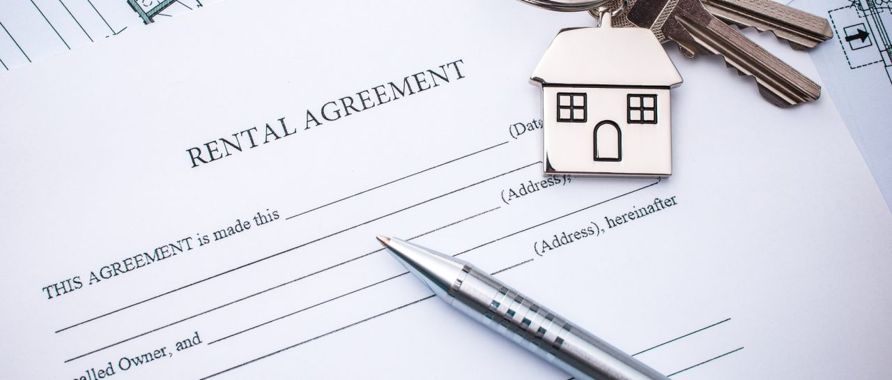Rental agreement for a month-by-month lease with a pen and key