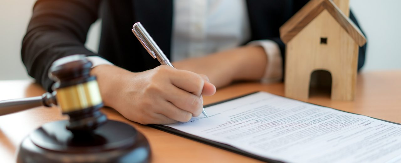 Woman signing a mortgage lien document with a gavel next to her.