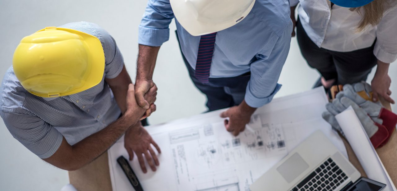 Team of one women architect and two men architects on a construction site. Men are shaking hands. Shot from above.