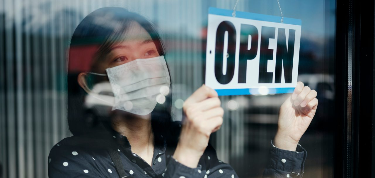A business owner changing the store sign to OPEN after being closed for a period of time due to social distancing guidelines related to Coronavirus.