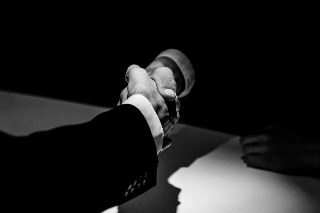 Black and white tone of anonymous business partners making handshake in dark shadow.
