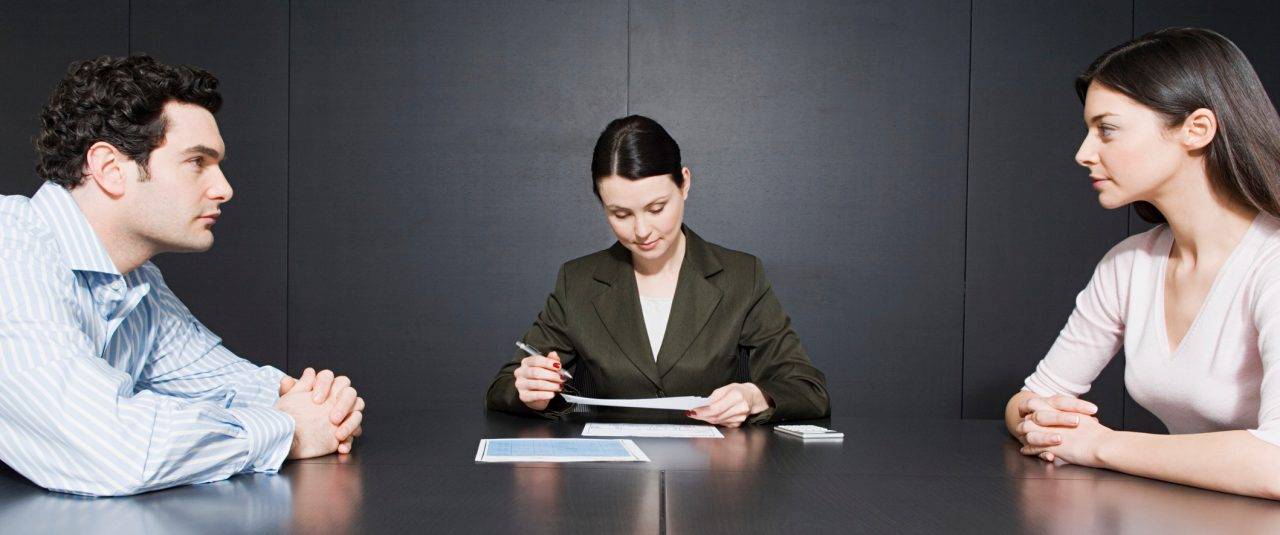 Divorcing Spouses Sitting at a Table With a Mediator