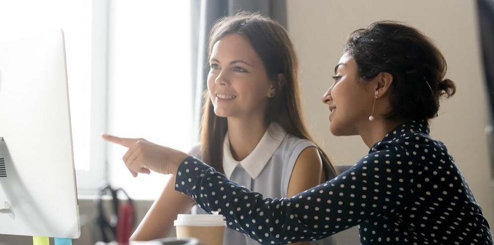 Smiling millennial diverse colleagues discussing online work together, happy caucasian female intern listening to indian mentor explaining computer task training employee, office mentoring concept